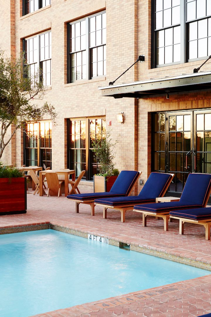 <p>One of the courtyards includes a pool, built to fit in seamlessly with the hotel's design and featuring upholstered seating in shades of navy blue. </p>