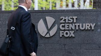 A pedestrian passes in front of signage outside Twenty-First Century Fox Inc. headquarters in New York, U.S., on Wednesday, May 3, 2017. Twenty-First Century Fox Inc. is scheduled to release earnings figures on May 10. Photographer: Alexander F. Yuan/Bloomberg via Getty Images