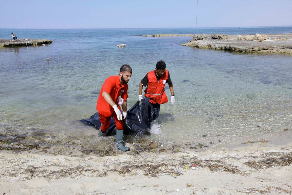 Rescuers carry a bag containing the body of a migrant at the coast of Tajoura, east of Tripoli, Libya,...