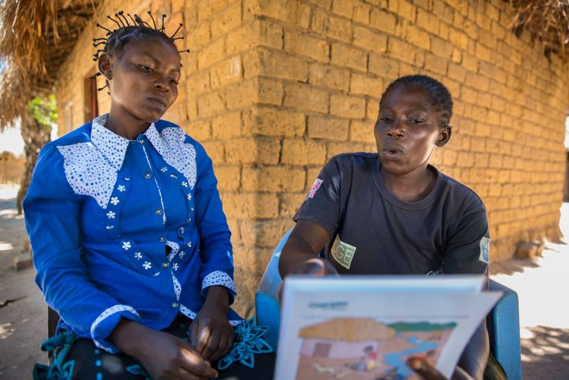 "Joelle Inamulongo (left) getting hygiene information from Adele (right), a community volunteer, or ""Animateur,"" trained by Co"