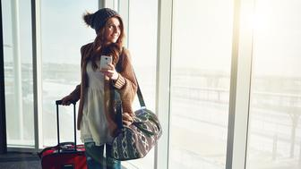 Shot of a young woman standing in an airport with her luggage staring outside while holding her cellphone