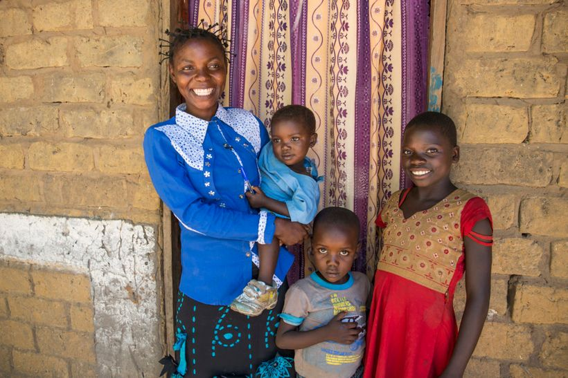 Joelle Inamulongo with her children at their home in the village of Katchambuyu, DRC. She is a beneficiary of the WASH projec
