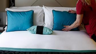 A chambermaid prepares a bed in a guest room in this arranged photograph taken inside a Hotel Indigo hotel, operated by InterContinental Hotels Group Plc, in London, U.K., on Thursday, May 8, 2014. InterContinental, the owner of the Holiday Inn and Crowne Plaza brands, said it will pay a special dividend in July after selling the Mark Hopkins San Francisco and an 80 percent stake in the New York Barclay for about $394 million in March. Photographer: Simon Dawson/Bloomberg via Getty Images