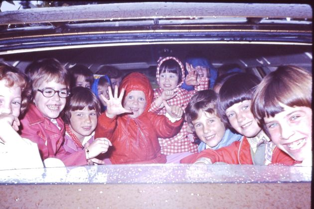Heidi sits center, in the red hooded coat. Her little sister is next to her, wearing the gingham coat....