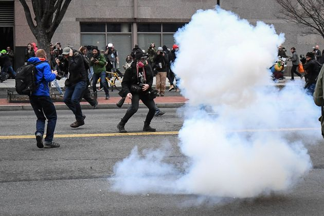 Protesters and journalists scramble as stun grenades are deployed by police during a protest in Washington...
