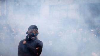 An activist stands amid smoke from a stun grenade while protesting against U.S. President Donald Trump on the sidelines of the inauguration in Washington, D.C. January 20, 2017. REUTERS/Adrees Latif