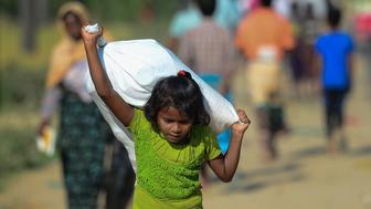 A Rohingya Muslim refugee child carries relief aid through Balukhali refugee camp in the Ukhia district of Bangladesh on November 20, 2017. An estimated 618,000 Muslim Rohingya have fled mainly Buddhist Myanmar since a military crackdown was launched in Rakhine in August triggered an exodus, straining resources in the impoverished country. / AFP PHOTO / Munir UZ ZAMAN        (Photo credit should read MUNIR UZ ZAMAN/AFP/Getty Images)