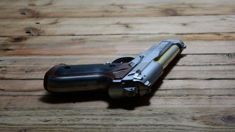 the old handgun  on  brown wooden table