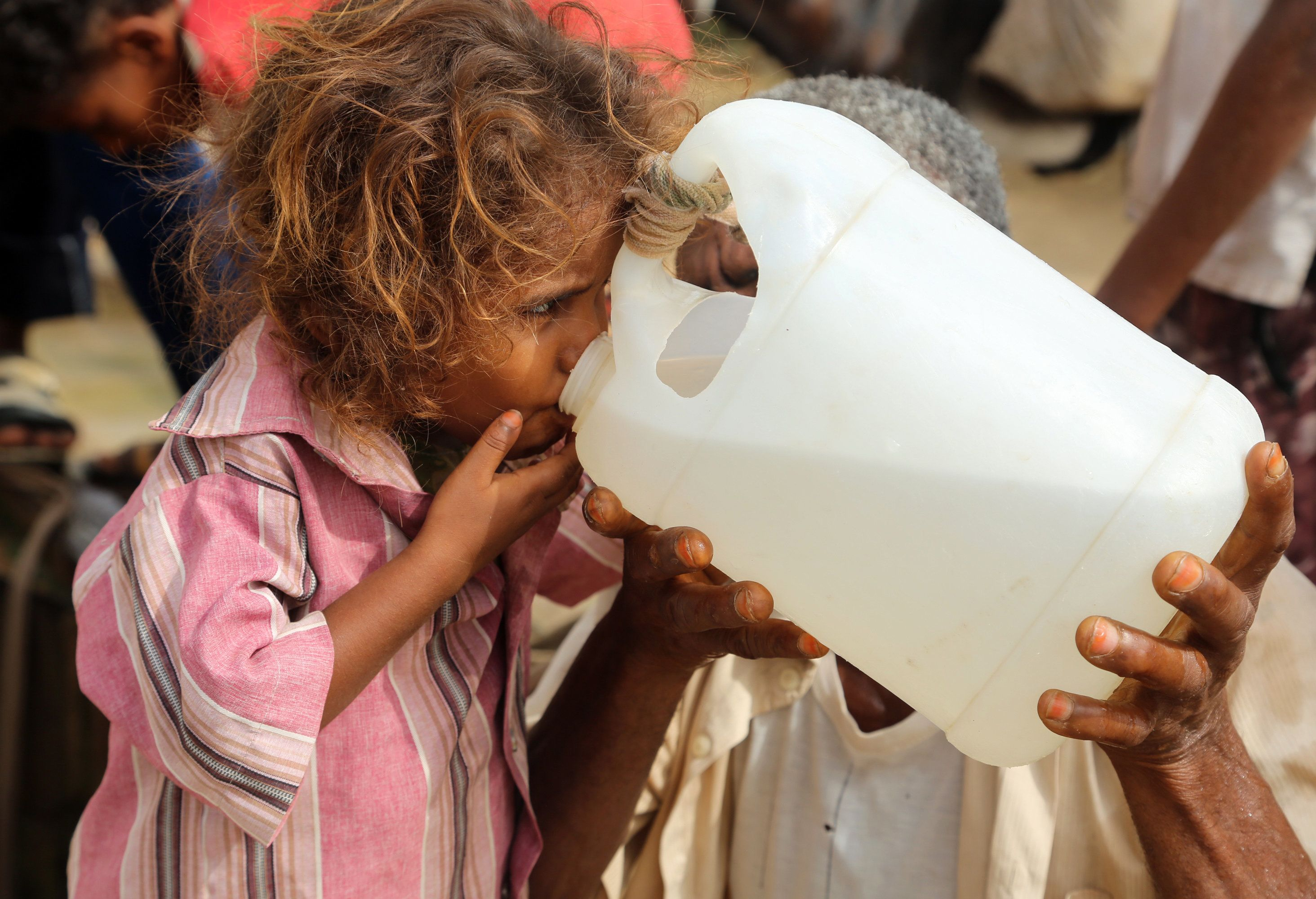A Yemeni girl drinks water collected from a well in an impoverished village on the outskirts of the port city of Hodeidah, on July 23, 2017, as the region has been facing acute water shortages due to drought conditions. / AFP PHOTO / Abdo HYDER        (Photo credit should read ABDO HYDER/AFP/Getty Images)