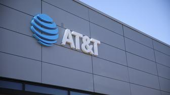 Signage is displayed outside of an AT&T Inc. store in Newport Beach, California, U.S., on Thursday, Aug. 10, 2017. AT&T Inc. shares surged the most in more than eight years after the telecommunications giant posted a surprise wireless subscriber gain in the second quarter, showing it can fend for itself in a cutthroat price war. An offer for unlimited wireless data, bundled with discounted streaming-TV service, helping AT&T bide its time while awaiting regulatory approval to transform into a media powerhouse through the $85.4 billion purchase of Time Warner Inc. Photographer: Patrick T. Fallon/Bloomberg via Getty Images
