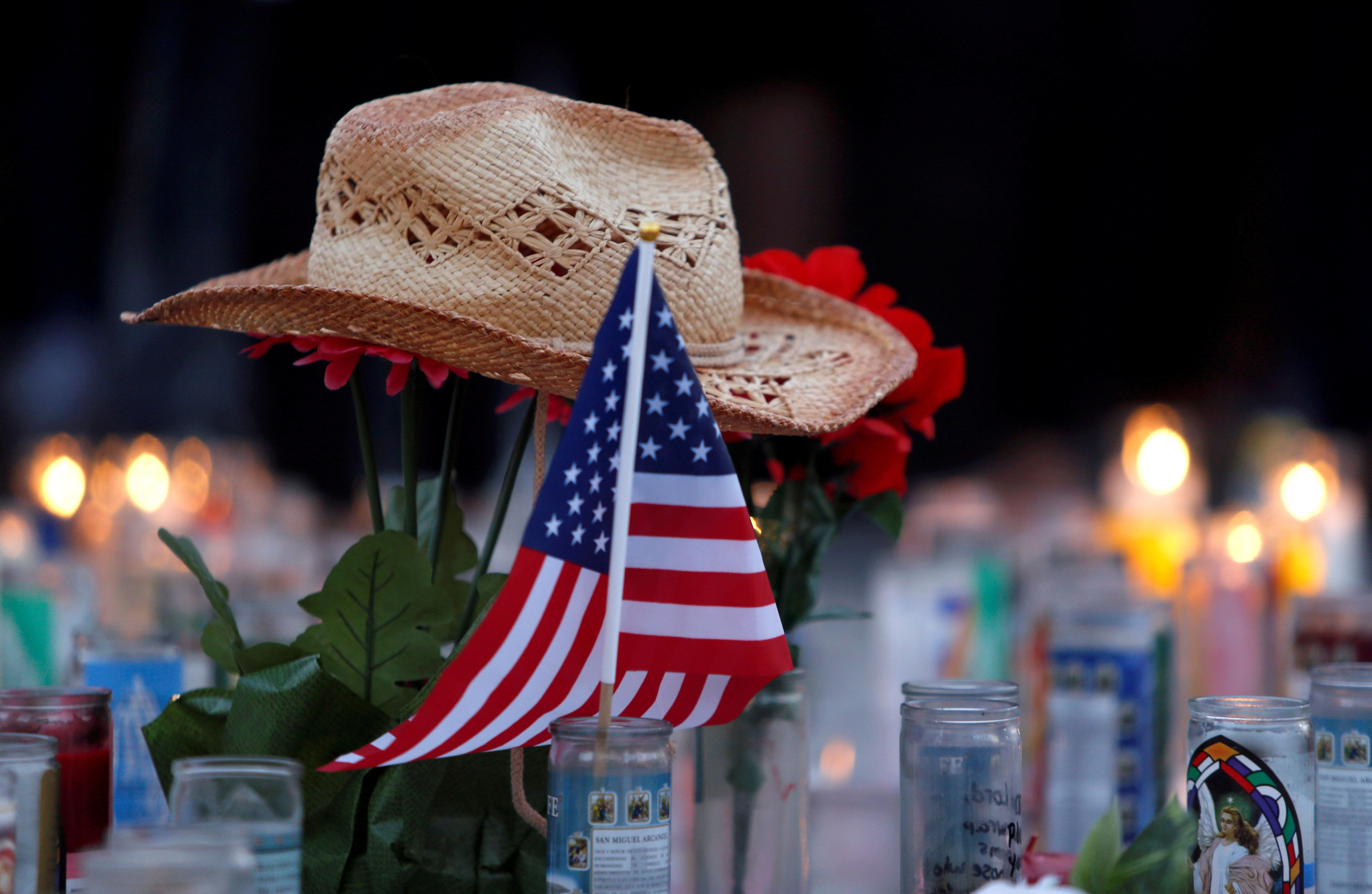 A hat rests on flowers in a makeshift memorial during a vigil marking the one-week anniversary of the October 1 mass shooting in Las Vegas, Nevada U.S. October 8, 2017. REUTERS/Las Vegas Sun/Steve Marcus     TPX IMAGES OF THE DAY