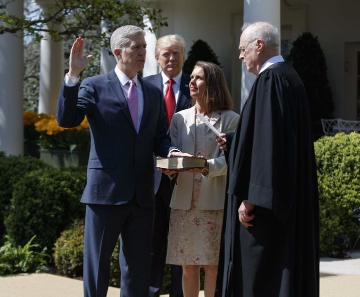 President Trump observes as Associate Justice Neil Gorsuch (left), flanked by his wife, is sworn in by Associate Justice Anth