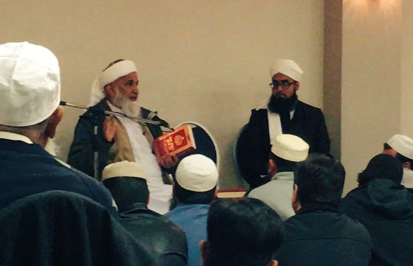 Maulana Rafiq Khan, one of the event organizers, holding a copy of the Quran that he wants removed from American libraries.