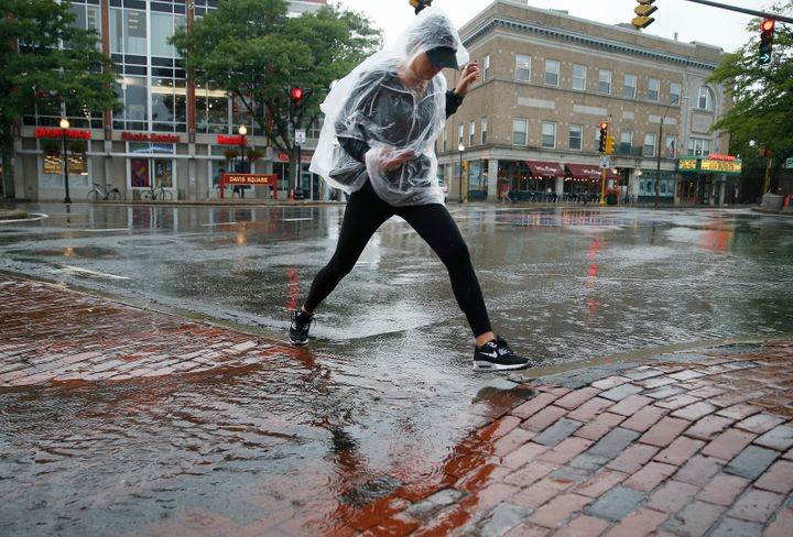 A woman jumps over a puddle after a heavy rain in Davis Square in Somerville, MA, in September