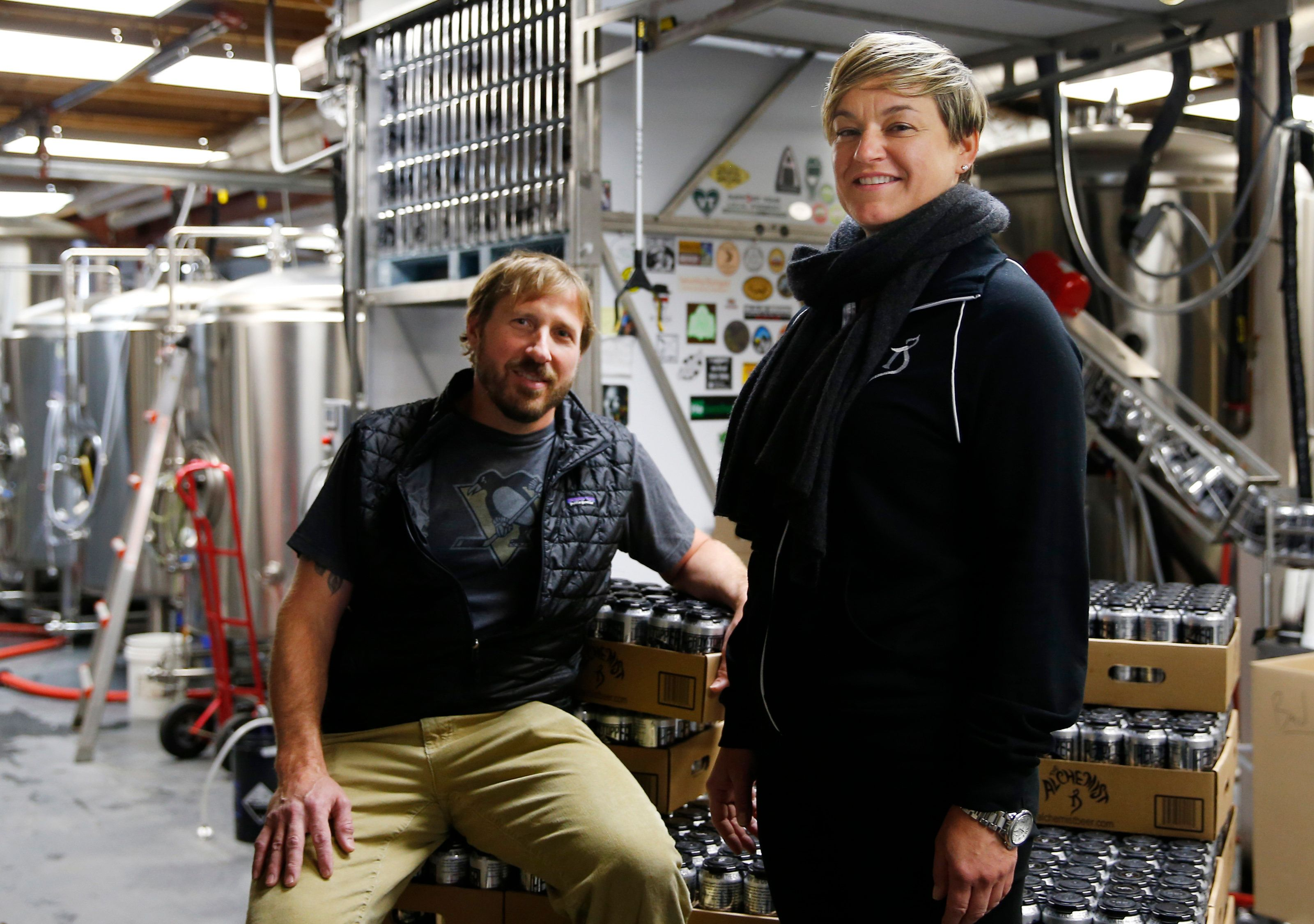 WATERBURY, VT - JANUARY 21: Alchemist brewery owners John and Jen Kimmich pose for a portrait while sitting on stacks of Heady Topper in Waterbury, VT on Jan. 21, 2015. (Photo by Jessica Rinaldi/The Boston Globe via Getty Images)
