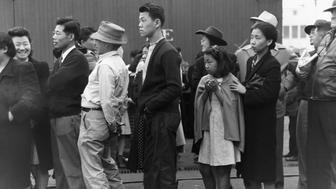 Japanese-Americans in Los Angeles, California, watching a train take their friends and relatives to the Owens Valley internment camp. Japanese-Americans were evacuated from certain West Coast areas under US Army War Emergency Order. April 1942. (Photo by © CORBIS/Corbis via Getty Images)
