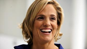 Olympic swimmer Dara Torres smiles during an interview in New York August 6, 2009. Olympic swimming heroine Torres pauses, her delicate hazel eyes narrow, and she stares at a tiny puddle of water that has splashed out of the pool. The inspirational 42-year-old Floridian badly wants to compete at the London Olympics in 2012 but ponders the potential deal-breakers -- her age, her health and her devotion to her three-year-old daughter Tessa. Picture taken August 6. To match FEATURE SWIMMING/TORRES    REUTERS/Jamie Fine (UNITED STATES SPORT SWIMMING)