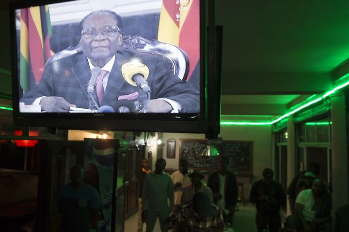 Zimbabweans watch a television broadcasting an address by President Robert Mugabe at Harare Sports Club in Harare on November