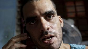 Cuban graffiti artist Danilo Maldonado speaks on his cellphone in his house in Havana, in this October 20, 2015 file photo.  REUTERS/Enrique De La Osa