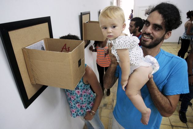 Cuban artist Danilo Maldonado Machado poses with his daugther during a photo exhibition in