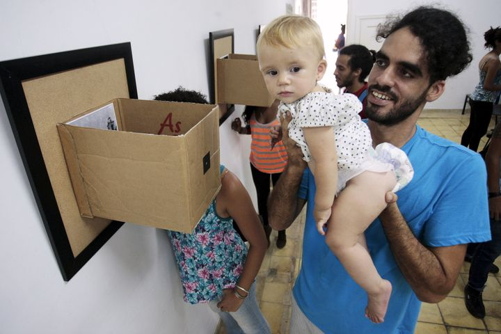Cuban artist Danilo Maldonado Machado poses with his daughter during a photo exhibition in Havana