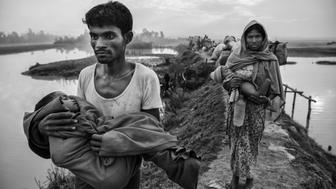 COX'S BAZAR, BANGLADESH - NOVEMBER 02: Rohingya Muslim refugees carry their children as they walk on an earthen berm after crossing the border from Myanmar into Bangladesh near the Naf River on November 2, 2017 near Anjuman Para in Cox's Bazar, Bangladesh. More than 600,000 Rohingya refugees have flooded into Bangladesh to flee an offensive by Myanmar's military that the United Nations has called 'a textbook example of ethnic cleansing'.  The refugee population continues to swell further, with thousands more Rohingya Muslims making the perilous journey on foot toward the border, or paying smugglers to take them across by water in wooden boats. Hundreds are known to have died trying to escape, and survivors arrive with horrifying accounts of villages burned, women raped, and scores killed in the 'clearance operations' by Myanmar's army and Buddhist mobs that were sparked by militant attacks on security posts in Rakhine state on August 25, 2017.  What the Rohingya refugees flee to is a different kind of suffering in sprawling makeshift camps rife with fears of malnutrition, cholera, and other diseases.  Aid organizations are struggling to keep pace with the scale of need and the staggering number of them - an estimated 60 percent - who are children arriving alone. Bangladesh, whose acceptance of the refugees has been praised by humanitarian officials for saving lives, has urged the creation of an internationally-recognized 'safe zone' where refugees can return, though Rohingya Muslims have long been persecuted in predominantly Buddhist Myanmar. World leaders are still debating how to confront the country and its de facto leader, Aung San Suu Kyi, a Nobel Peace Prize laureate who championed democracy, but now appears unable or unwilling to stop the army's brutal crackdown.  (Photo by Kevin Frayer/Getty Images)