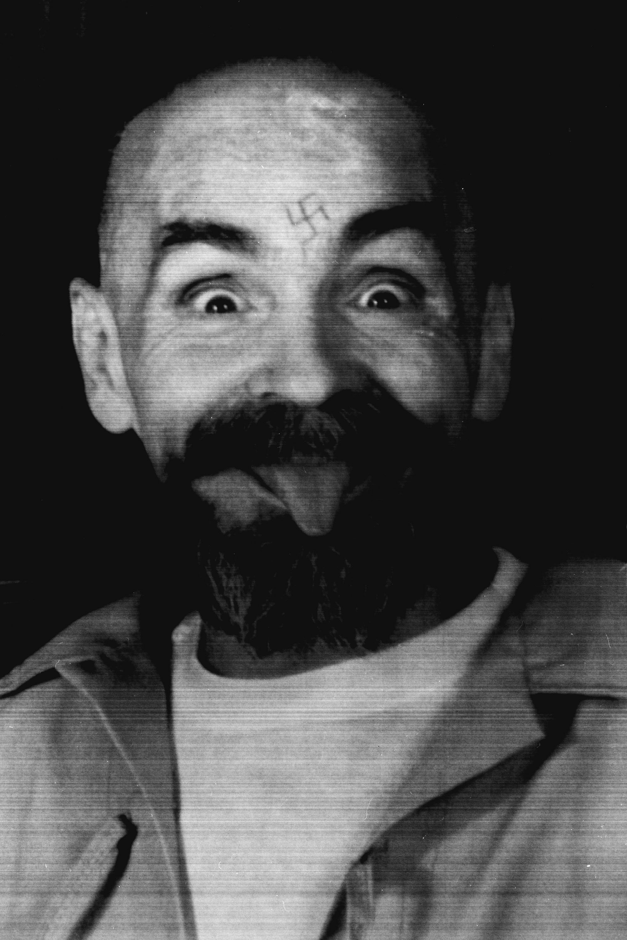 Charles Manson clowns around as he is led to his cell upon the conclusion of his exclusive interview with Reuters.  Charles Manson clowns around as he is led to his cell upon the conclusion of his exclusive interview with Reuters August 25, 1989. PP05070214 Reuters/Calvin Hom
