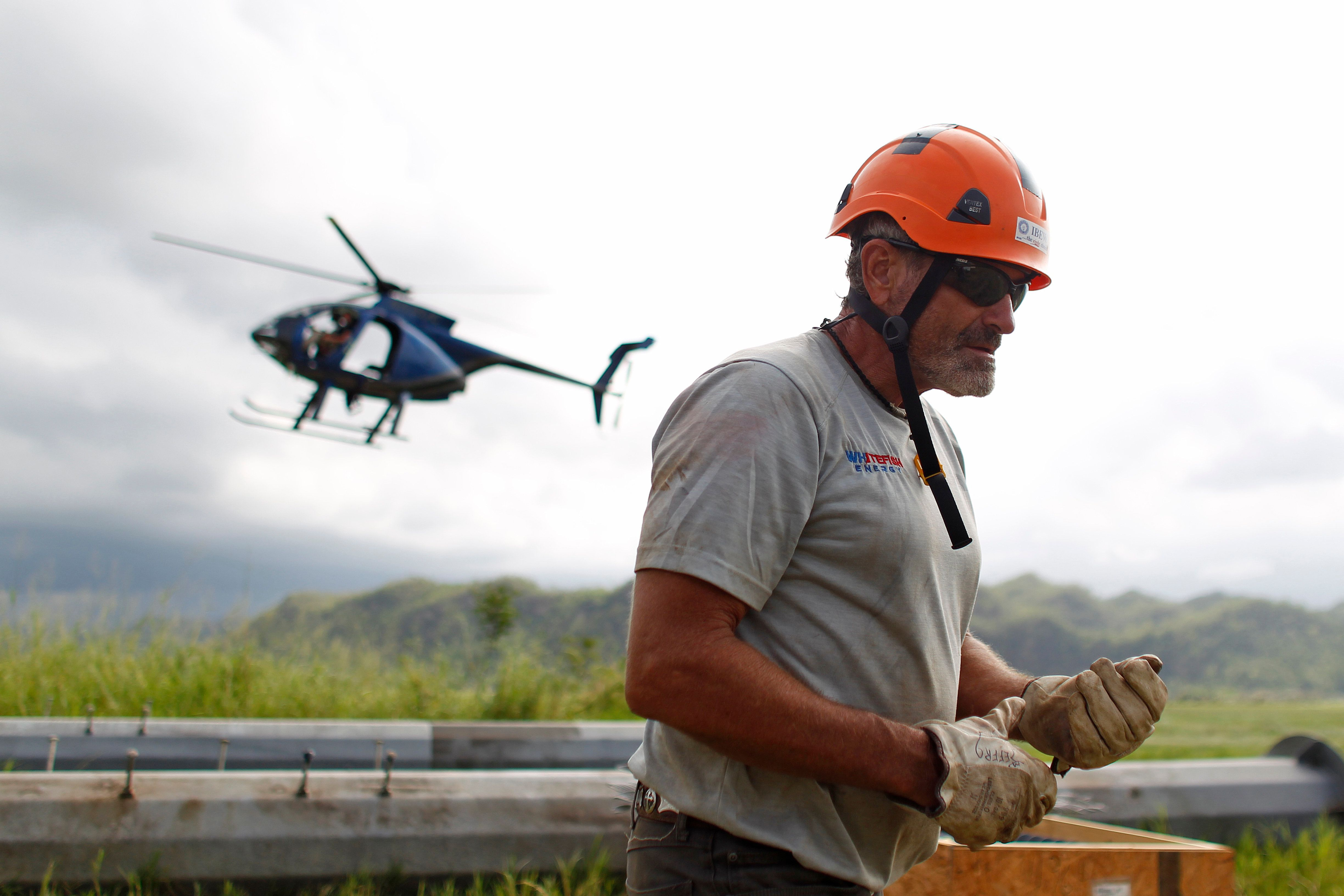 A helicopter from Whitefish Energy Holdings lands on site to pick up workers repairing power line towers after the passing of Hurricane Maria in Manati, Puerto Rico on October 31, 2017. Whitefish Energy had won a $300-million contract to help turn the lights back on in Puerto Rico, where some 80 percent of customers still lack power more than a month after Hurricane Maria ripped through the island. But Puerto Rico is scrapping the deal with the tiny American firm that fell under intense scrutiny the head of its power authority said on October 29, 2017. / AFP PHOTO / Ricardo ARDUENGO        (Photo credit should read RICARDO ARDUENGO/AFP/Getty Images)