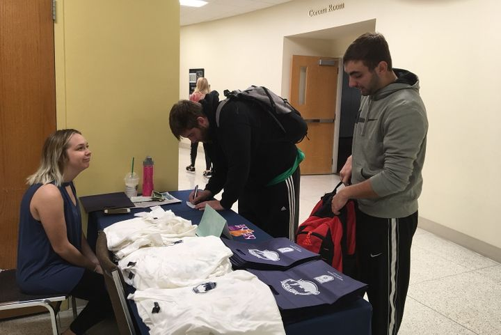"""Mount St. Joseph University student Monica Brucher looks on as students donate to a """"silent guest"""" fundraiser for the World F"""
