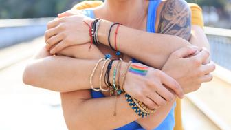 Two young girls embracing on bridge, one standing behind other. One with arm tattoo, other with multicolored flag on hand. Both with casual clothes. Focus on foreground.