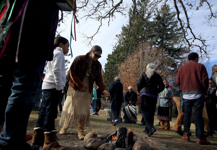 Mashpee Wampanoag tribe members sprinkle tobacco over a fire during a Native American Thanksgiving celebration on Nov. 23, 20