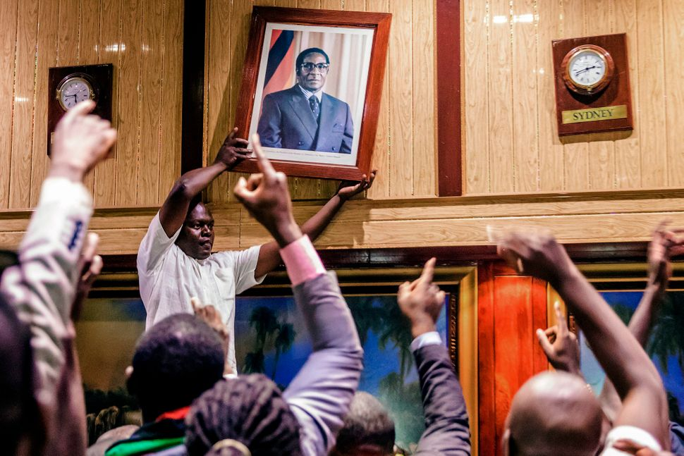 People removeMugabe'sportraitfrom the wall at the International Conference center.