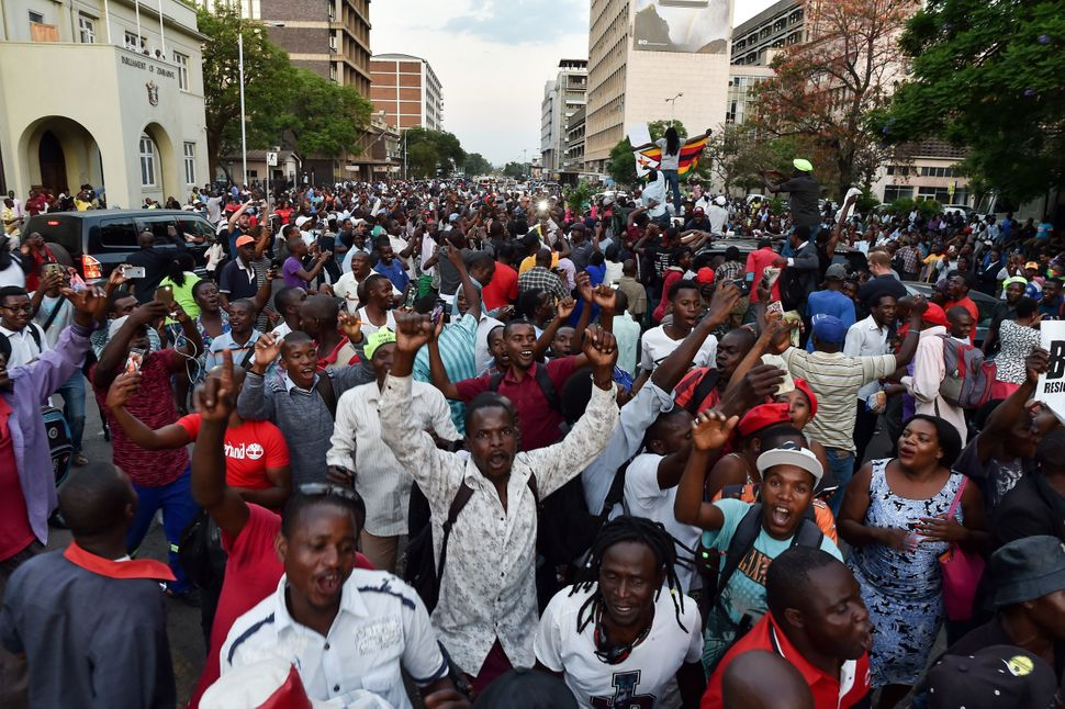 People celebrate in the streets of Harare after the resignation of Zimbabwe's president Robert Mugabe on Nov. 21.