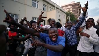 Zimbabweans celebrate after President Robert Mugabe resigns in Harare, Zimbabwe November 21, 2017. REUTERS/Mike Hutchings