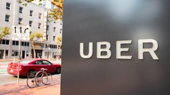 Sign with logo at the headquarters of car-sharing technology company Uber in the South of Market (SoMa) neighborhood of San Francisco, California, with red vehicle visible in the background parked on Market Street, October 13, 2017. SoMa is known for having one of the highest concentrations of technology companies and startups of any region worldwide. (Photo by Smith Collection/Gado/Getty Images)