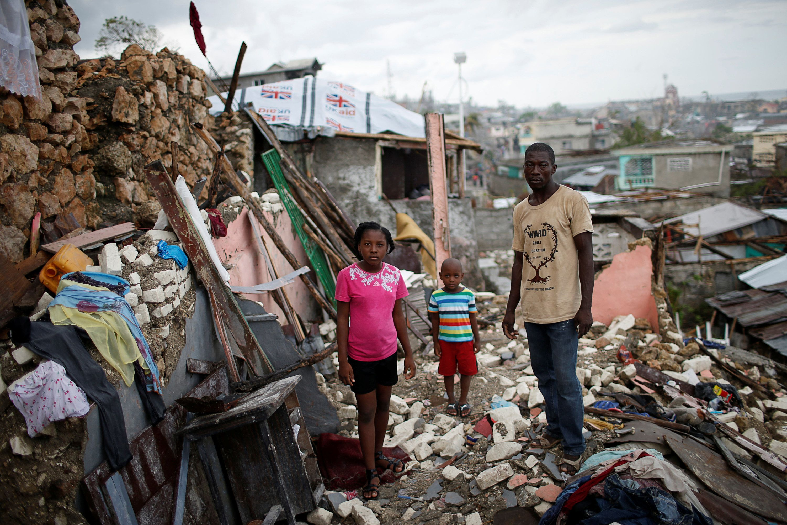 "Prenille Nord, 42, poses for a photograph with his children Darline and Kervins among the debris of their destroyed house after Hurricane Matthew hit Jeremie, Haiti, October 17, 2016. ""My house is completely destroyed, I have nothing left. Now we are homeless and I'm currently living in a shelter with my family but that makes no sense to me. I'm scared of the cholera. People around us are becoming sick, I really need help, so far we have not received any aid,"" said Nord. REUTERS/Carlos Garcia Rawlins          SEARCH ""HAITI PORTRAITS"" FOR THIS STORY. SEARCH ""WIDER IMAGE"" FOR ALL STORIES."