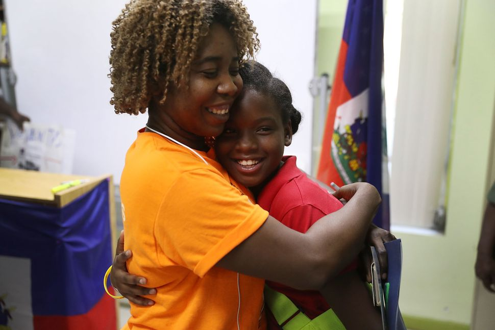 Santcha Etienne, left, hugs Ronyde Christina Ponthieux, 10, after she spoke at a news conference at the office of the Ha