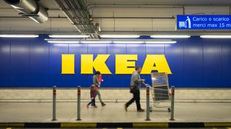 Chieti, Italy - November 19, 2016: A family walking in the car parking after shopping at Ikea store; the big sign of the store is in the background. Ikea is one of the largest (if not the largest)  ready-to-assemble furniture retailer.