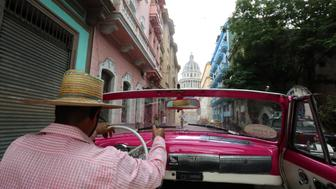 HAVANA, CUBA - OCTOBER 8: A classic car taxi driver makes his way to the Capitolio on October 8, 2017 in Havana, Cuba. (Photo by Gary Hershorn/Getty Images)