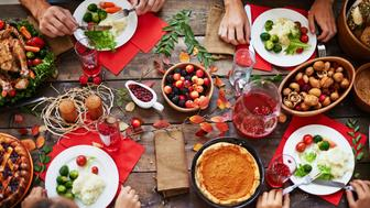 Above view of thanksgiving dinner and family eating at table