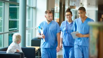 three junior doctors walking along a hospital corridor discussing case and wearing scrubs. A patient or visitor is sitting in the corridor as they walk past .