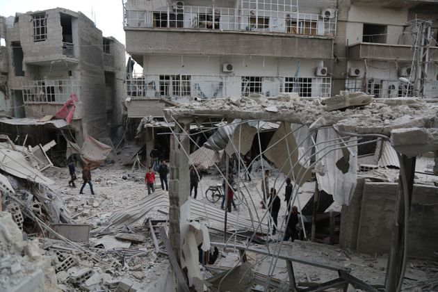 Syrians in eastern Ghouta inspect the damage after an airstrike reportedly carried out by the Assad...