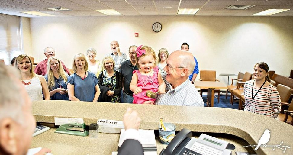 """""""As Grandpa held his new granddaughter, the judge joined in the celebration by allowing the little girl to tap his gavel on h"""