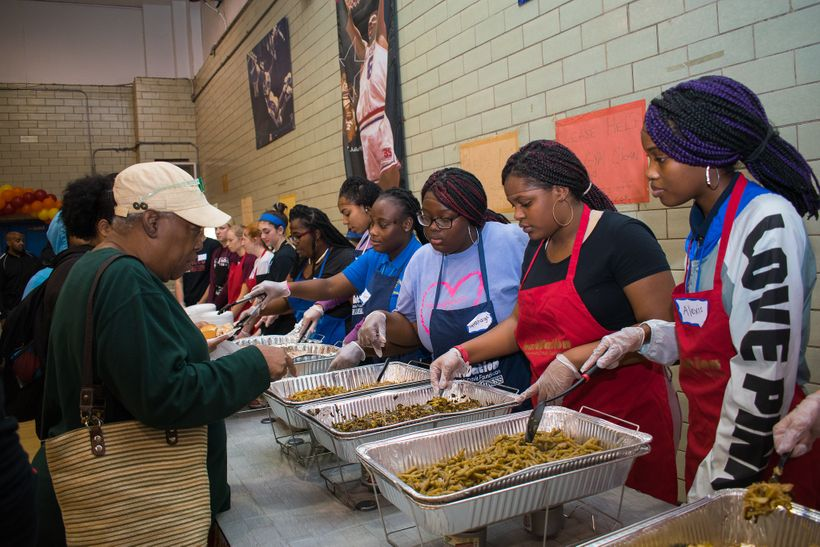 Volunteers serve warm meals at the Food From Heaven Thanksgiving event.