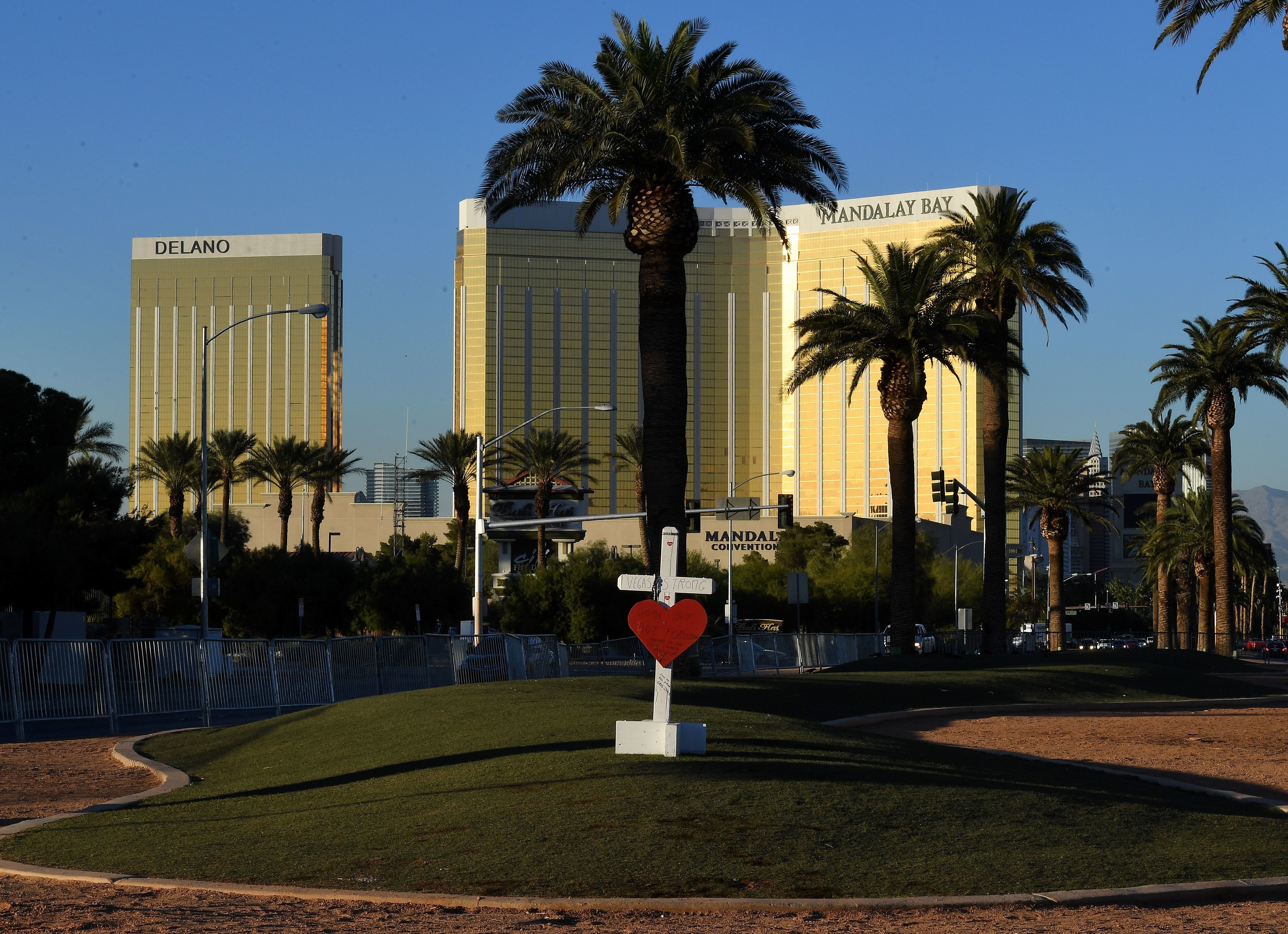 A solitary cross remains at a memorial site in front of the Mandalay Hotel (back) for the 58 victims of the worst shooting in US history, in Las Vegas, Nevada on November 15, 2017. The other 57 crosses have been moved from the iconic 'Welcome to Las Vegas' sign location to the Clark County museum. The US has been hit by a wave of other mass shootings since the October 1st Las vegas massacre. / AFP PHOTO / Mark RALSTON        (Photo credit should read MARK RALSTON/AFP/Getty Images)
