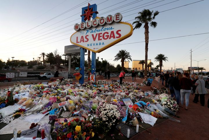 "Flowers and other tributes to the victims of the Las Vegas massacre pile up at the iconic ""Welcome to Las Vegas"" sign."