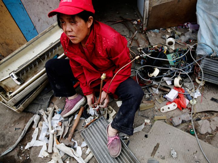 A woman dismantles e-waste for scrap at Dongxiaokou village in Beijing, a major center for recycling old electrical and electronic goods.