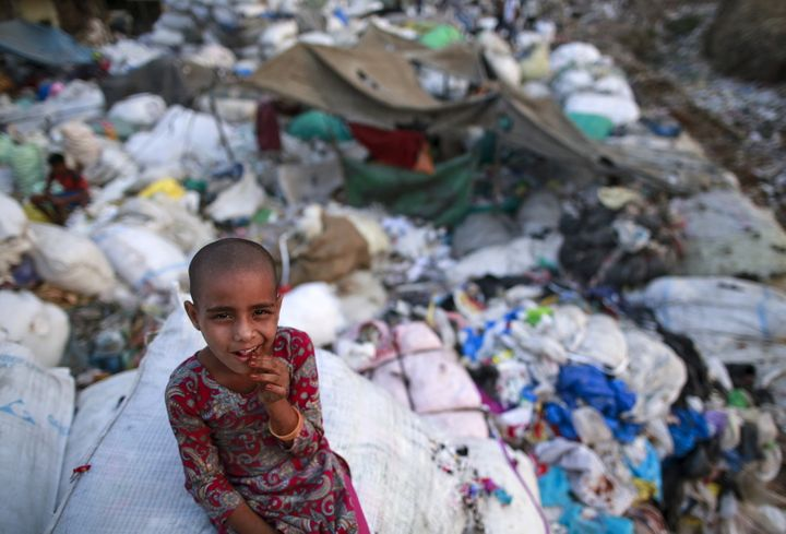 A girl sits on a sack of discarded clothes at a slum in Mumbai, India, on April 20, 2016.
