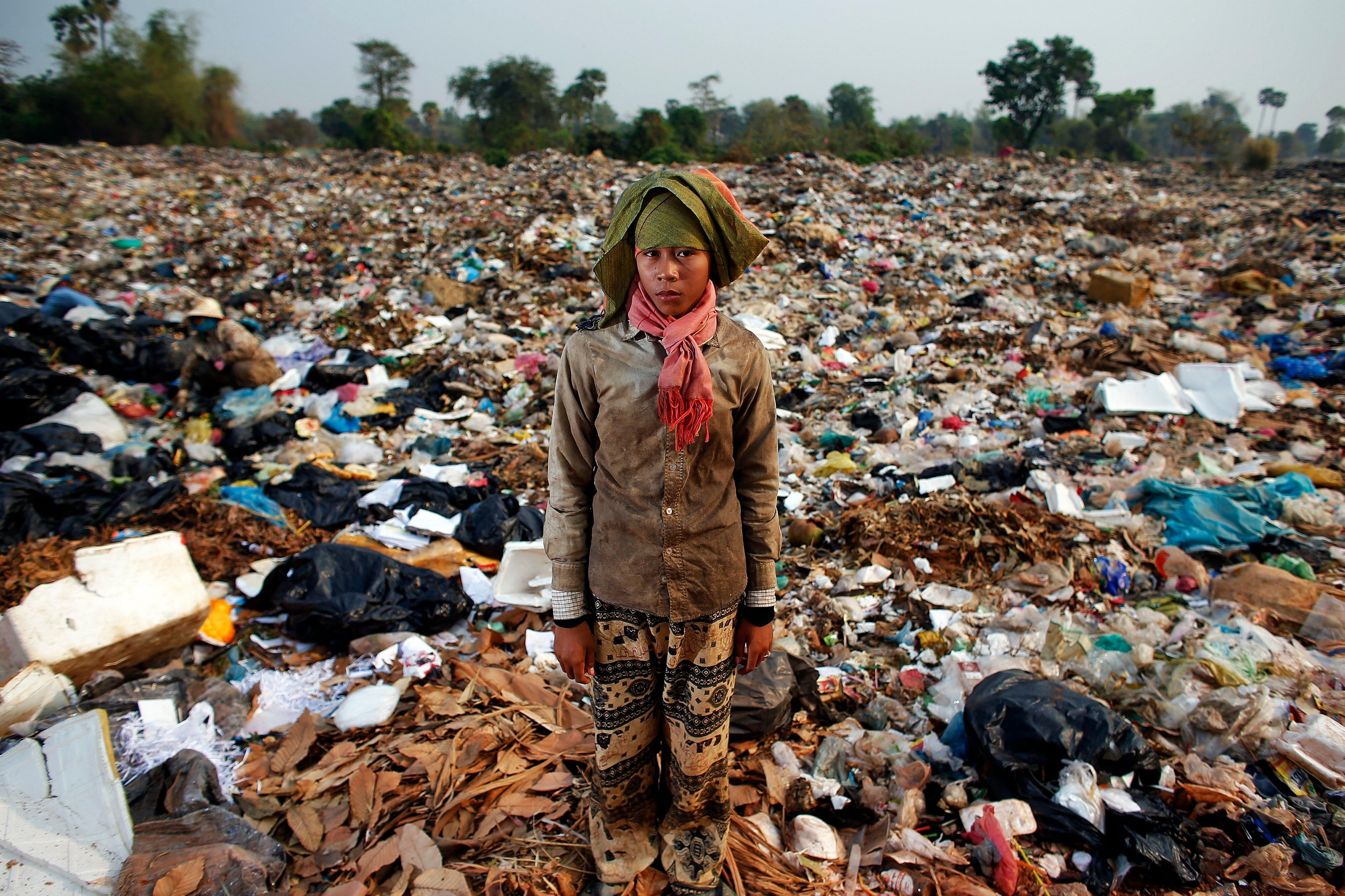 Chan Thy, a 15-year-old girl, poses for a picture while collecting usable items at landfill dumpsite outside Siem Reap March 19, 2015. She works non-stop at the dumpsite earning 2 USD a day after finishing six-grade primary school two years ago. Anlong Pi, an eight-hectare dumpsite situated close to the famous Cambodian resort province of Siem Reap, has recently become a tourist attraction in its own right. Sightseers pose for pictures with children who scavenge scraps for a living, making between $0.25 and $2 per day, according to a representative of a company overseeing the waste. Michelle Obama is due to visit to Cambodia to promote Let Girls Learn, a worldwide initiative that aims to help adolescent girls attend school.   REUTERS/Athit Perawongmetha  PICTURE 10 OF 23 FOR WIDER IMAGE STORY 'LIVING ON RUBBISH'  SEARCH 'ANLONG PI' FOR ALL IMAGES