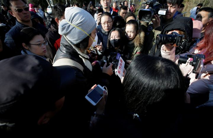A parent is surrounded by the media outside RYB New World Kindergarten in Beijing on Nov. 24, 2017.